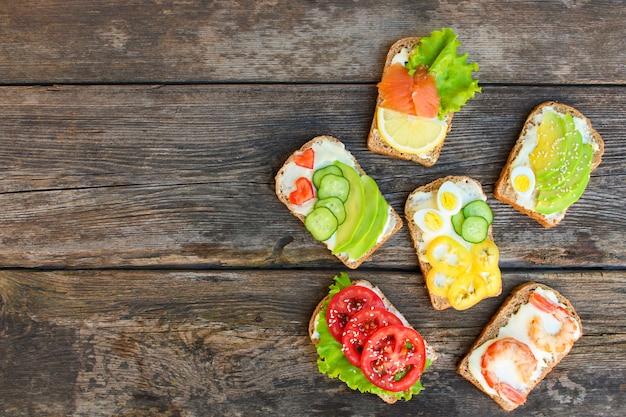 Von den verschiedenen sandwichen auf dem alten hölzernen hintergrund. Premium Fotos