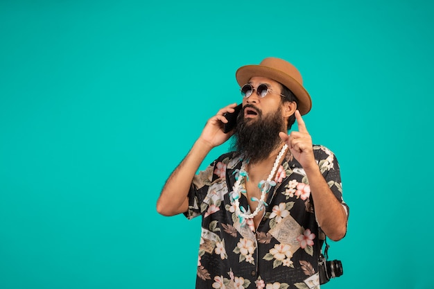 Von einem glücklichen langen bartmann, der einen hut, ein gestreiftes hemd tragend trägt und halten ein telefon auf einem blau. Kostenlose Fotos