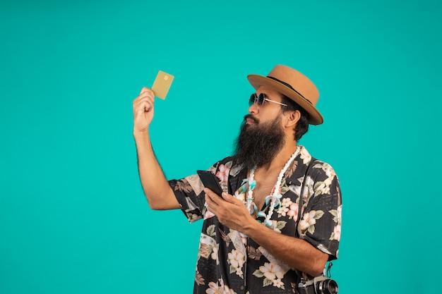 Von einem glücklichen langen bartmann, der einen hut, ein gestreiftes hemd tragend trägt und halten eine goldene kreditkarte auf einem blau. Kostenlose Fotos