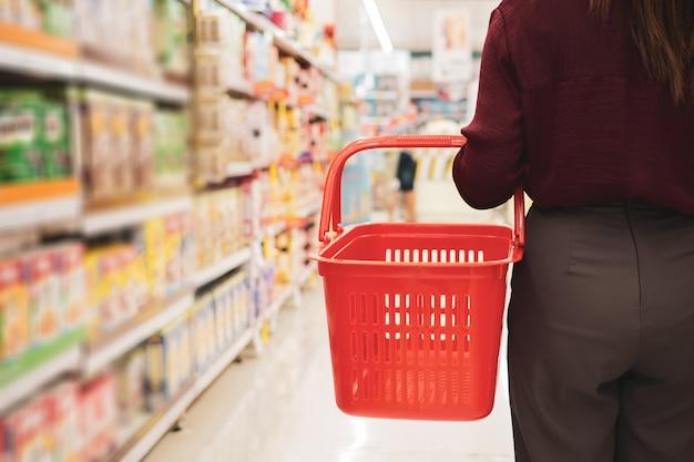 Von junger frau mit korb im supermarkt geerntet Premium Fotos