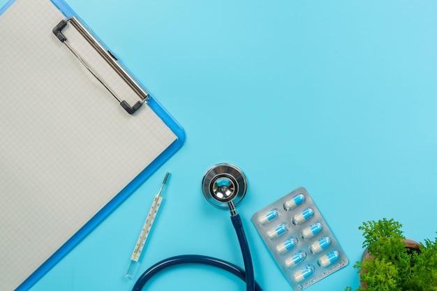 Von medikamenten, medizinischen hilfsgütern neben schreibtafeln und arztwerkzeugen auf einem blauen hintergrund. Kostenlose Fotos