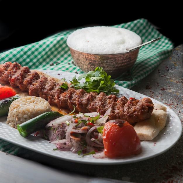 Von oben adana kebab mit reis und gebratenem gemüse sowie gehackten zwiebeln und ayran Kostenlose Fotos