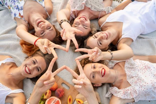 Von oben betrachten. die gesellschaft von schönen freundinnen hat spaß und genießt ein picknick im freien Premium Fotos