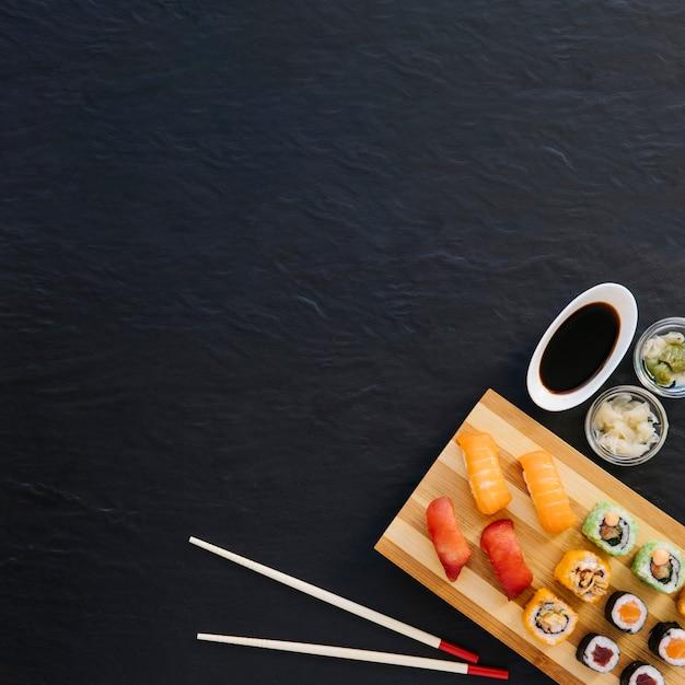 Von oben essstäbchen und gewürze in der nähe von sushi Kostenlose Fotos