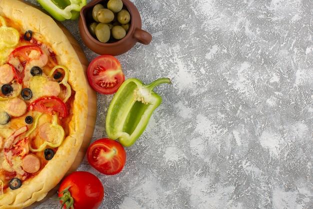 Von oben gesehen köstliche käsige pizza mit olivenwürsten und tomaten auf dem grauen schreibtisch fast-food-italienisches teigmehl Kostenlose Fotos