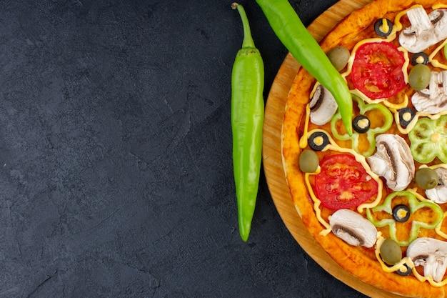 Von oben gesehen köstliche pilzpizza mit paprika-oliven und pilzen der roten tomaten, die alle innen auf dem dunklen hintergrund der lebensmittelpizza italienisch geschnitten werden Kostenlose Fotos