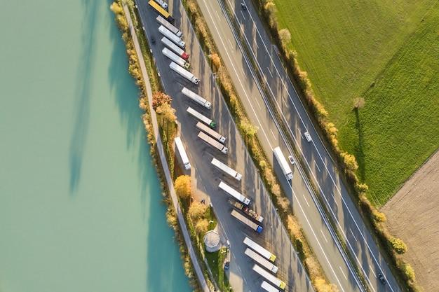 Von oben nach unten luftaufnahme der autobahn zwischen autobahn mit schnellem verkehr und parkplatz mit geparkten lkw-lkws. Premium Fotos