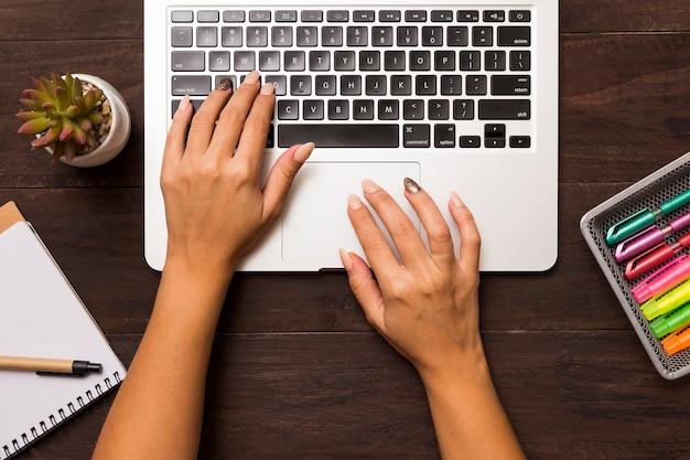 Von oben von den weiblichen händen, die an laptop arbeiten Kostenlose Fotos
