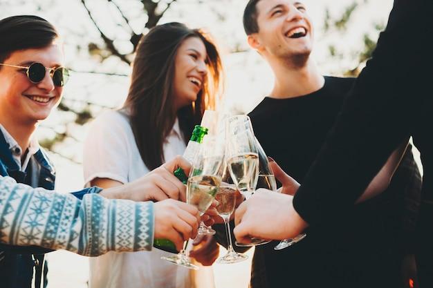Von unten aufnahme von jungen menschen, die mit anonymen freunden lachen und an alkohol trinken, während sie gemeinsam in der natur feiern Premium Fotos