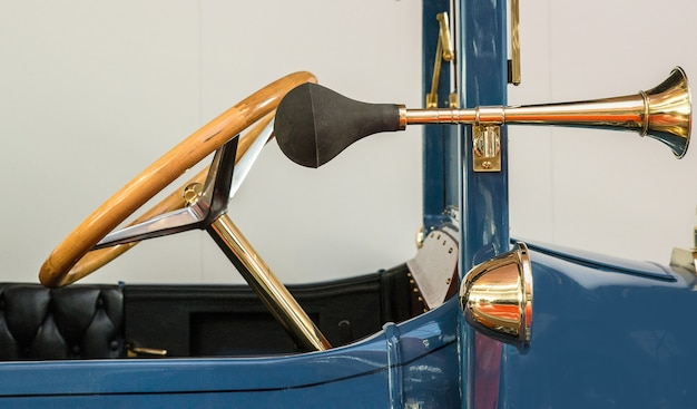 Vor einem blauen oldtimer mit einem antiken goldenen lenkrad und einer separaten hupe Kostenlose Fotos