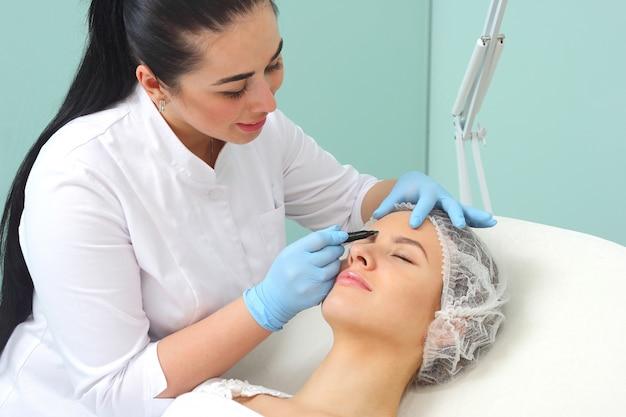 Vorbereitung des gesichts des patienten auf einen kosmetischen eingriff. Premium Fotos