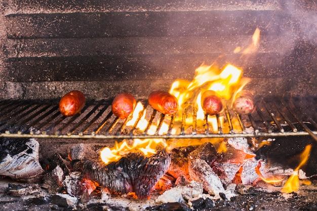 Vorbereitung von würsten auf barbecue-grill Kostenlose Fotos