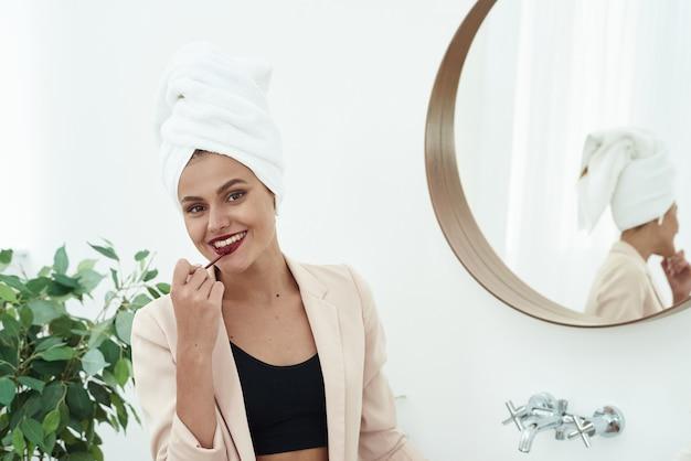 Vorbereitungen für das date. porträt einer schönen frau, färbt ihre lippen lippenstift burgund, in den spiegel schauend. Premium Fotos