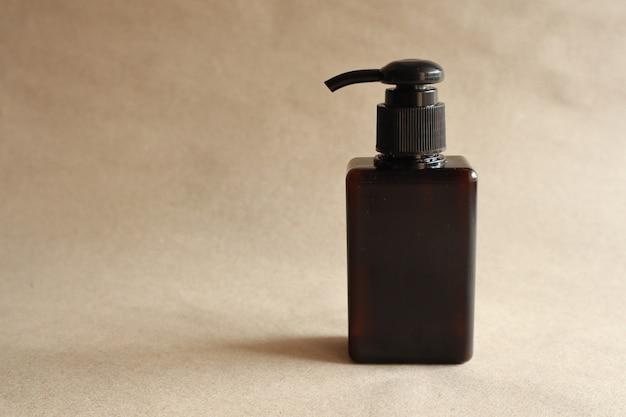 Vorbildliches bild einer braunen flasche mit einer pressungskappe auf braun Premium Fotos