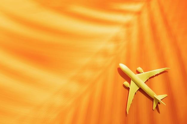 Vorbildliches flugzeug, flugzeug auf orange mit kopienraum und tropisches palmblatt Premium Fotos