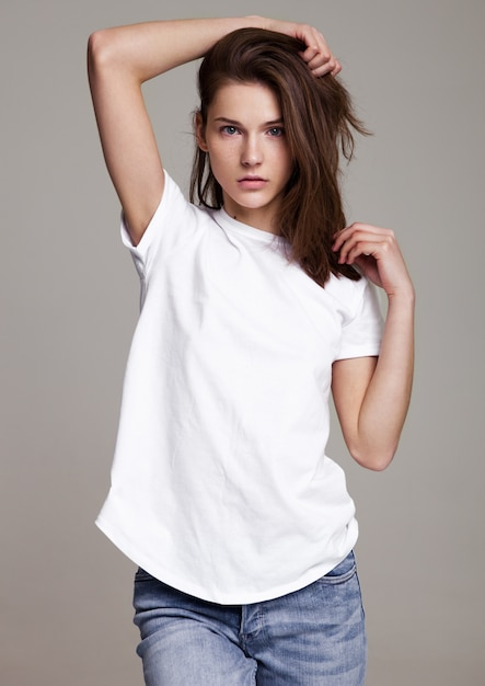 Vorbildliches testporträt mit dem jungen schönen mode-modell, das auf grauem hintergrund aufwirft. trägt weißes t-shirt und jeans. Premium Fotos