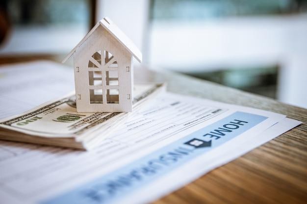 Vorbildliches weißes haus auf dollarbanknote. immobilienkonzept für versicherungen und immobilieninvestitionen. Premium Fotos