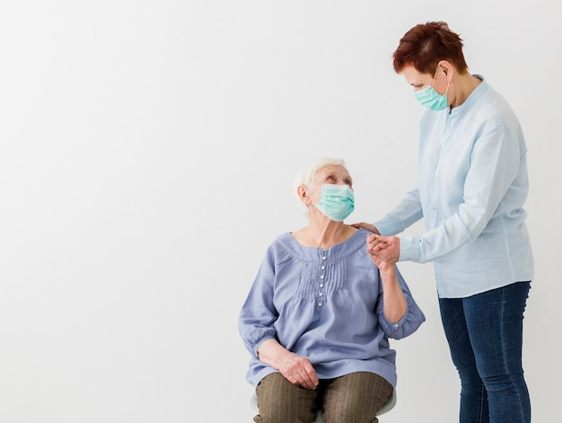 Vorderansicht älterer frauen mit medizinischen masken und kopierraum Kostenlose Fotos