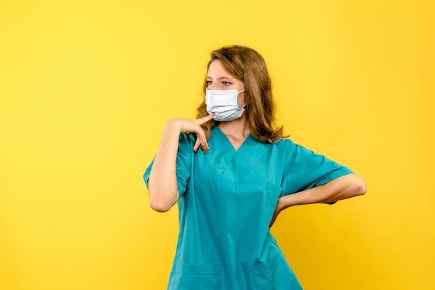 Vorderansicht ärztin in maske auf gelbem raum Kostenlose Fotos