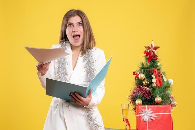 Vorderansicht ärztin stehend und hält dokumente auf gelbem schreibtisch mit weihnachtsbaum und geschenkboxen Kostenlose Fotos