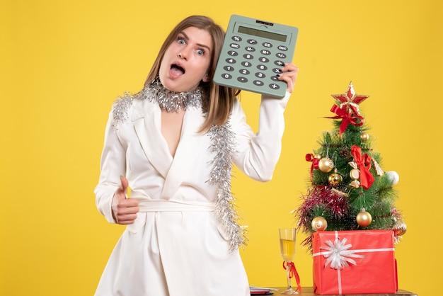Vorderansicht ärztin stehend und hält rechner auf gelb mit weihnachtsbaum und geschenkboxen Kostenlose Fotos
