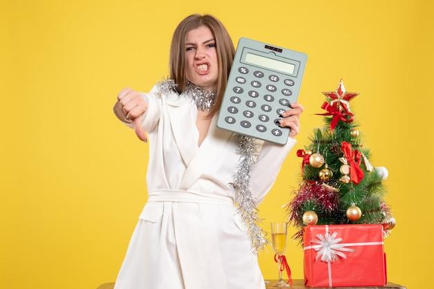Vorderansicht ärztin stehend und hält rechner auf gelbem hintergrund mit weihnachtsbaum und geschenkboxen Kostenlose Fotos