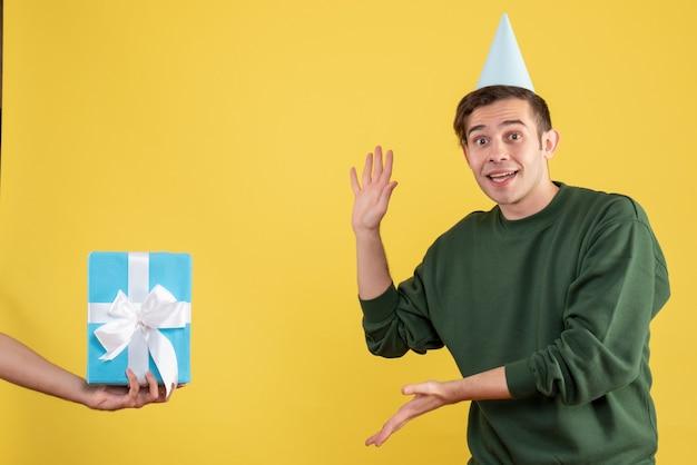 Vorderansicht aufgeregter junger mann, der das geschenk in der menschlichen hand auf gelb zeigt Kostenlose Fotos