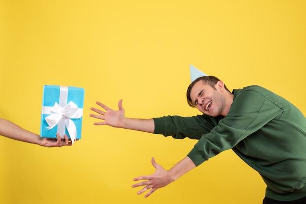 Vorderansicht aufgeregter junger mann, der versucht, das geschenk in der menschlichen hand auf gelb zu fangen Kostenlose Fotos