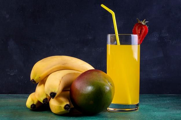 Vorderansicht bananen mit mango und einem glas orangensaft Kostenlose Fotos