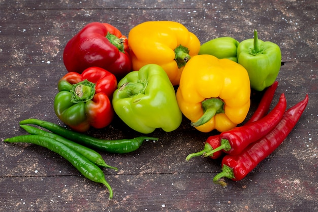 Vorderansicht bunte paprika mit paprika auf der braunen hintergrundgemüsefarbe Kostenlose Fotos
