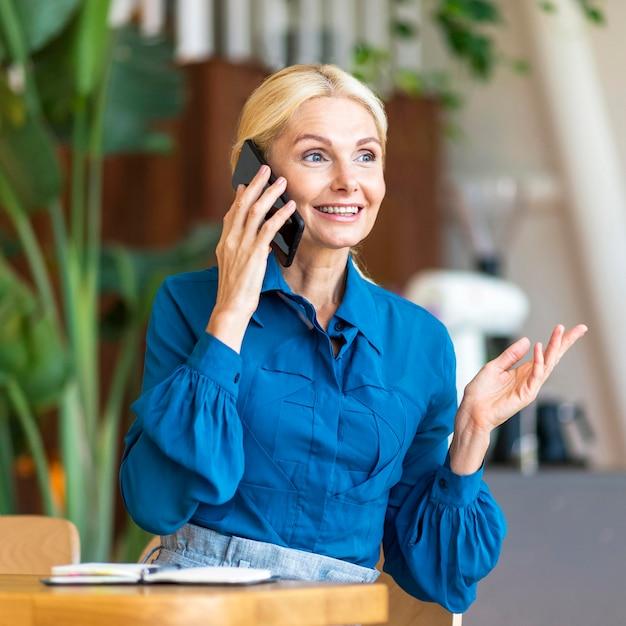 Vorderansicht der älteren frau, die am telefon während der arbeit spricht Kostenlose Fotos