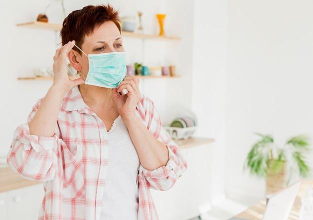 Vorderansicht der älteren frau, die medizinische maske aufsetzt Kostenlose Fotos