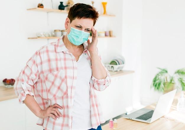 Vorderansicht der älteren frau, die medizinische maske trägt und sich nicht gut fühlt Kostenlose Fotos