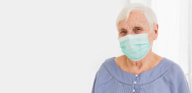 Vorderansicht der älteren frau mit medizinischer maske und kopienraum Kostenlose Fotos