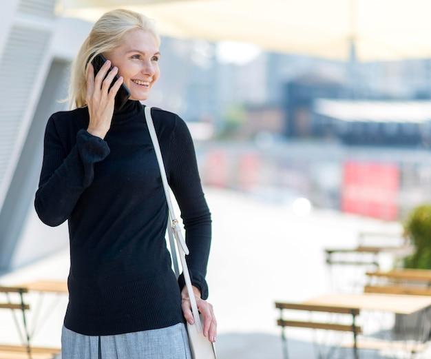 Vorderansicht der älteren geschäftsfrau des smileys auf einem telefonanruf im freien Kostenlose Fotos