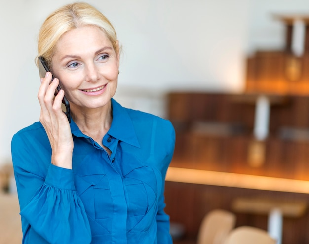 Vorderansicht der älteren geschäftsfrau des smileys, die am telefon spricht Kostenlose Fotos