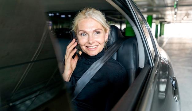 Vorderansicht der älteren geschäftsfrau des smileys, die das telefon im auto spricht Kostenlose Fotos