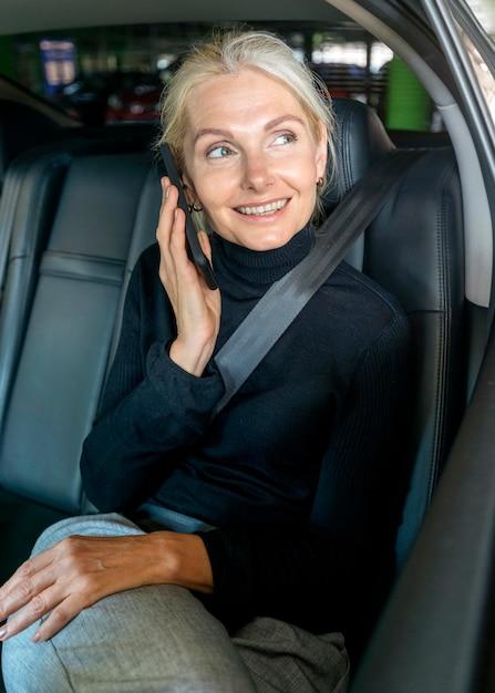 Vorderansicht der älteren geschäftsfrau, die das telefon im auto spricht Kostenlose Fotos