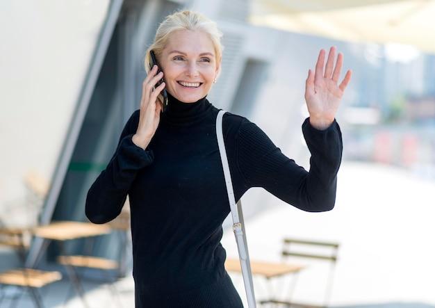 Vorderansicht der älteren smileyfrau im freien auf einem telefonanruf und winken Kostenlose Fotos