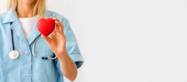 Vorderansicht der ärztin mit stethoskop, das herzform mit kopienraum hält Premium Fotos