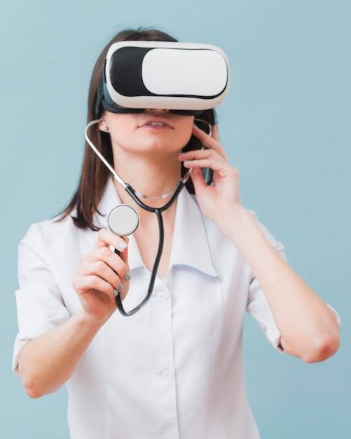 Vorderansicht der ärztin unter verwendung des virtual-reality-headsets und des stethoskops Kostenlose Fotos