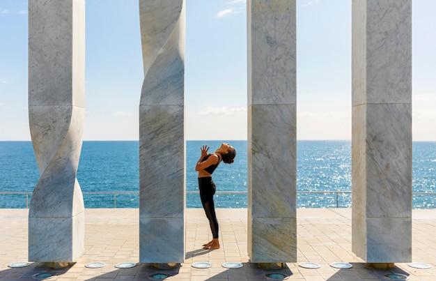 Vorderansicht der afroamerikanerfrau yoga auf küste tuend Premium Fotos