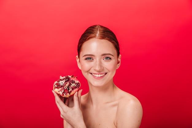 Vorderansicht der bezaubernden frau, die lächelt und saftigen granat hält. studioaufnahme des sorglosen ingwermädchens mit granatapfel. Kostenlose Fotos
