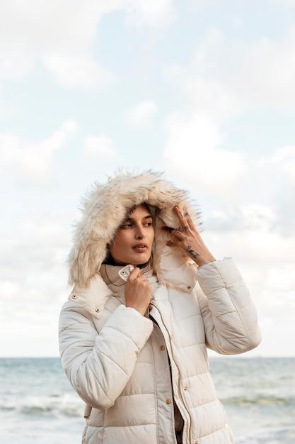 Vorderansicht der frau am strand mit winterjacke und kopierraum Kostenlose Fotos