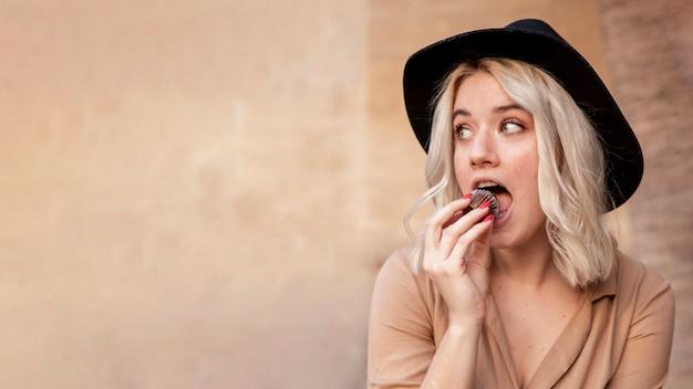 Vorderansicht der frau, die cupcake mit kopienraum isst Kostenlose Fotos