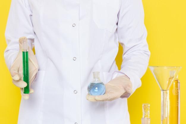 Vorderansicht der frau, die flaschen mit chemischen lösungen hält Kostenlose Fotos