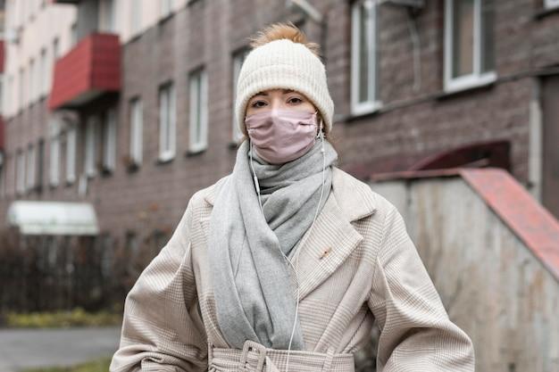 Vorderansicht der frau, die medizinische maske in der stadt trägt Kostenlose Fotos