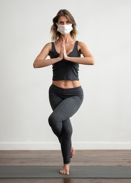 Vorderansicht der frau mit der medizinischen maske, die yoga tut Kostenlose Fotos