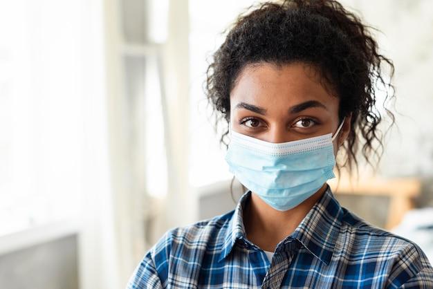 Vorderansicht der frau mit medizinischer maske und kopienraum Kostenlose Fotos