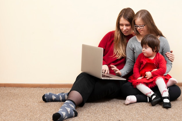 Vorderansicht der frau und der kinder mit down-syndrom, die laptop betrachten Kostenlose Fotos